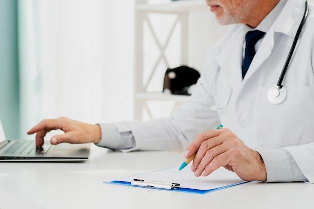 彼のラップトップで研究を行う医師