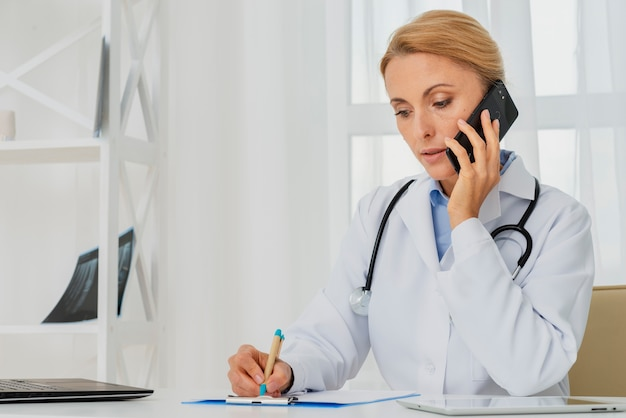 机に座って電話で話している医者