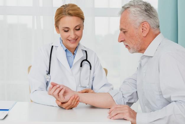 医者は患者の手を調べる