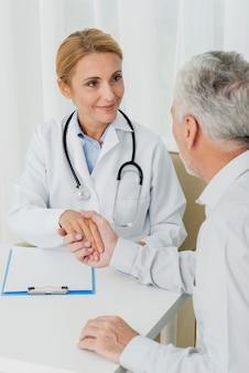 医者が患者の手を握って