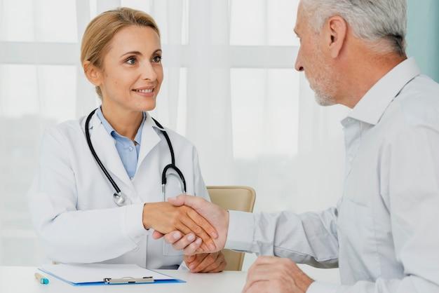 患者が医者の手を握って