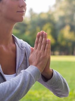 Крупным планом женщина медитирует на открытом воздухе