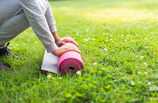 Женщина конца-вверх с розовой циновкой йоги