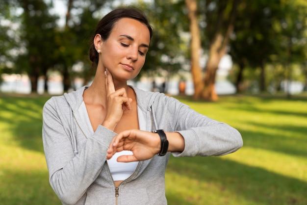 ミディアムショットの女性が彼女の脈拍を測定