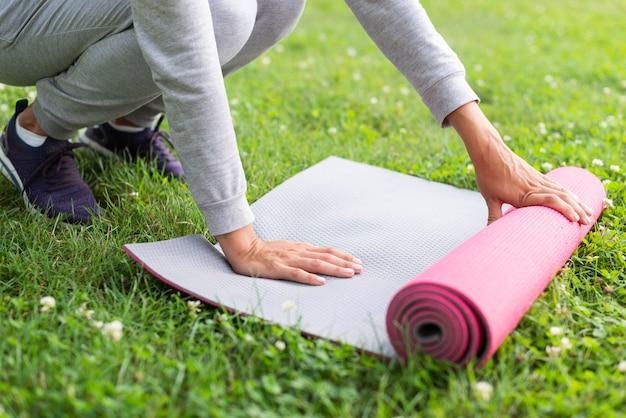Женщина конца-вверх подготавливая циновку йоги
