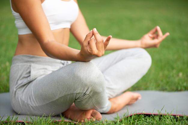 Крупным планом женщина практикует медитацию на открытом воздухе