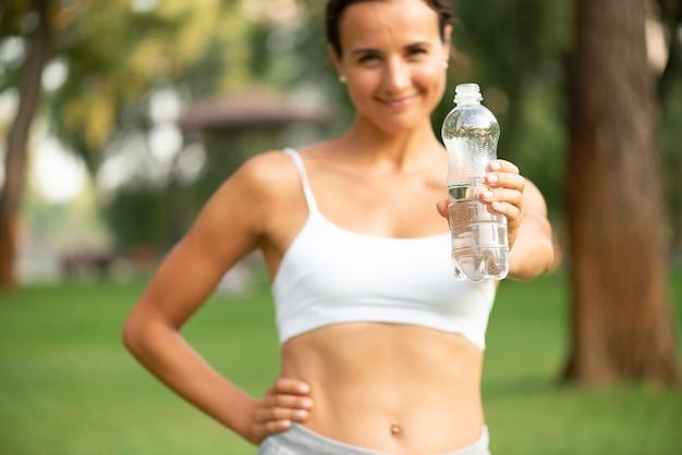 Женщина вид спереди держит бутылку с водой