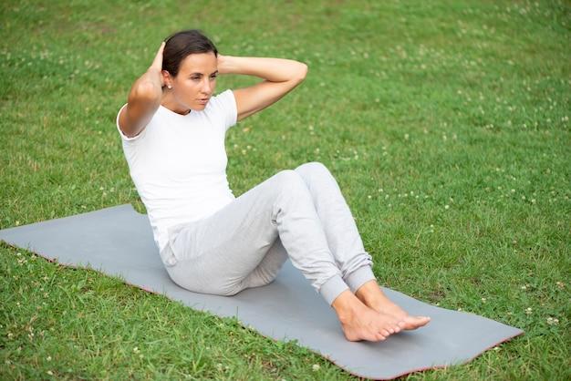 Полный выстрел женщина упражнения на коврик для йоги