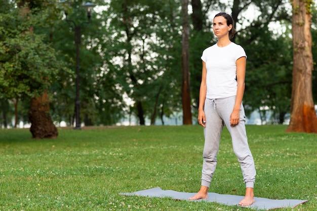 Полный выстрел женщина, стоящая на коврик для йоги