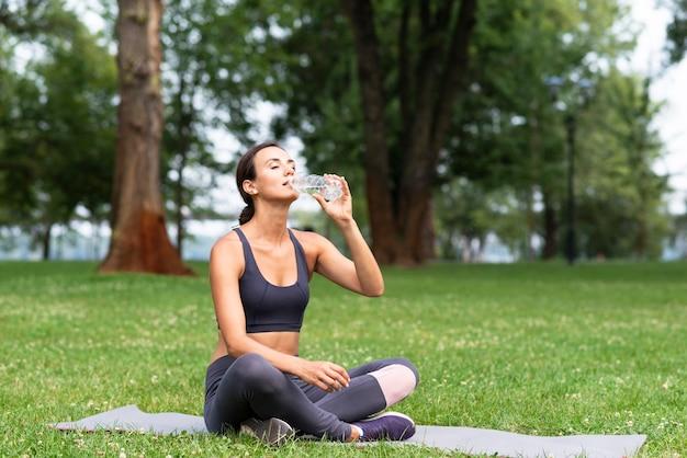 フルショットの女性が屋外で水を飲む