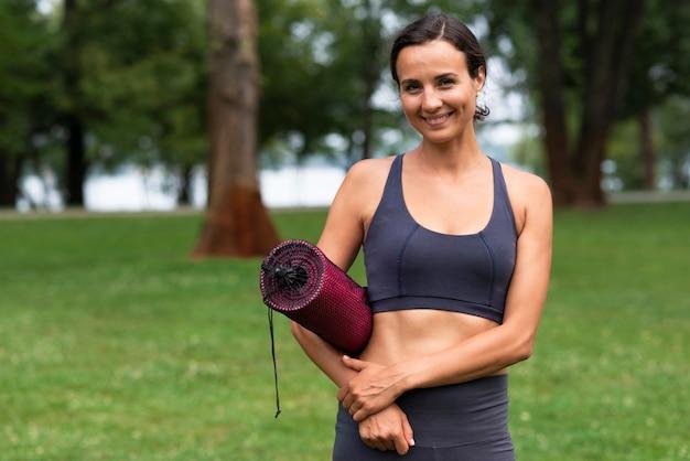 Женщина вид спереди держит коврик для йоги