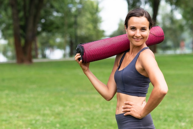 Женщина сбоку держит коврик для йоги