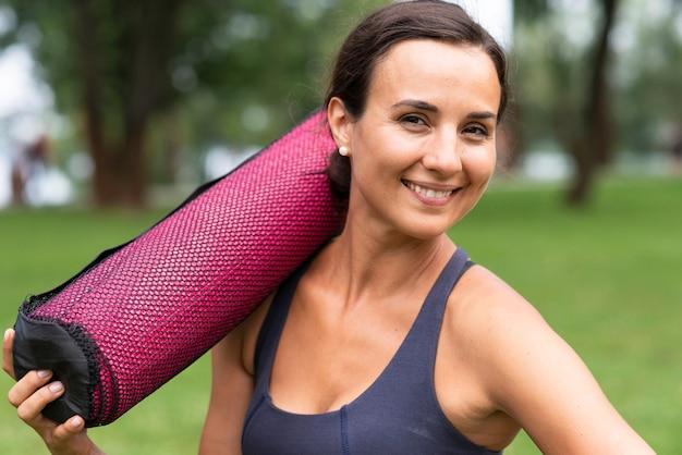 Вид сбоку смайлик женщина, держащая коврик для йоги
