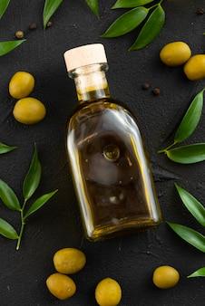 Крупным планом масло в бутылке на черном фоне