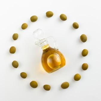 Бутылка оливкового масла в окружении зеленых оливок