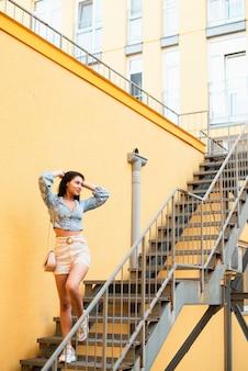 Женщина стоит на лестнице и смотрит в сторону