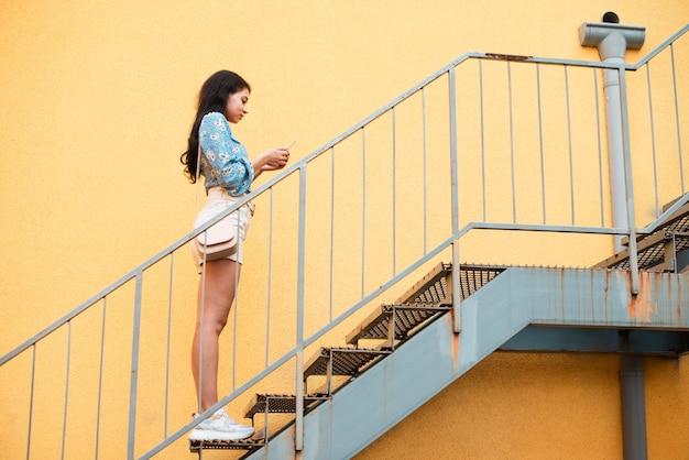 Боком девушка стоит на лестнице