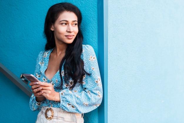 Женщина держит телефон и смотрит в сторону