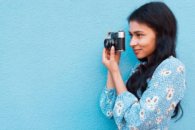 Боком женщина смотрит на свою камеру фото