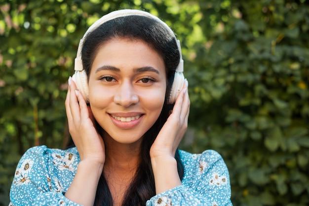 彼女のヘッドフォンを保持している女性のクローズアップの肖像画