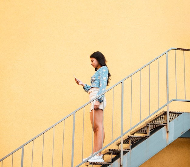 Боком женщина, стоя на лестнице