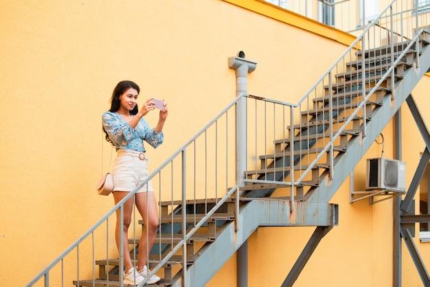 Длинный выстрел женщины, стоя на лестнице и фотографировать
