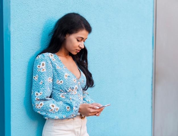 彼女の携帯電話に取り組んでいる花のシャツを持つ女性