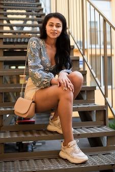 階段に座っている女性のフルサイズの体