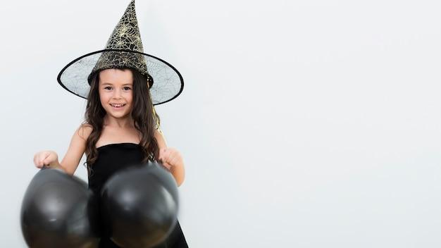 Вид спереди маленькая девочка в костюме ведьмы на хэллоуин