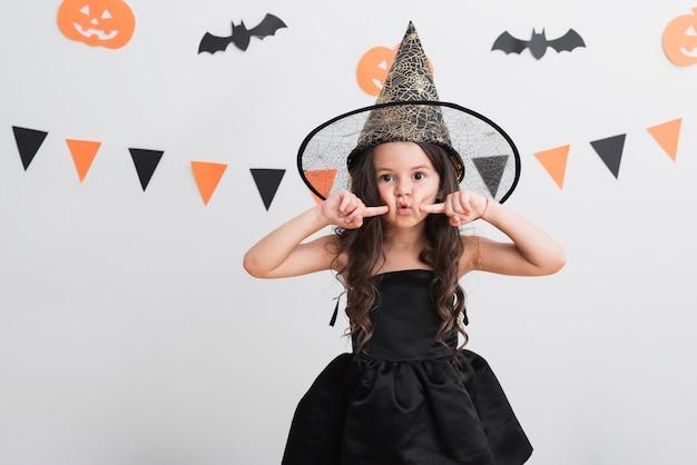 ハロウィーンの魔女の衣装の少女を正面します。