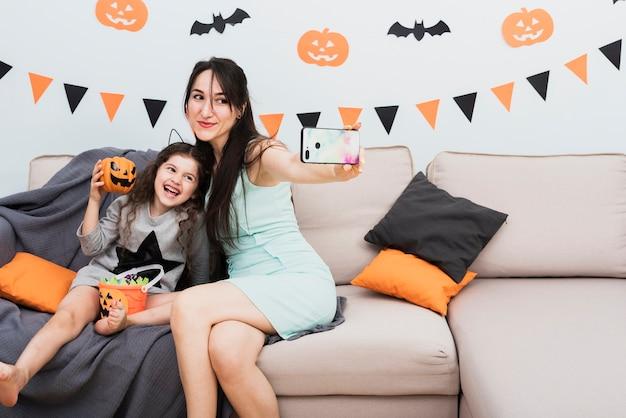 Мать, принимая селфи с дочерью на хэллоуин