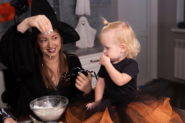若い女性と台所の小さな子供