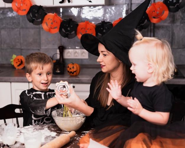 ハロウィーンクッキーを作る母親と彼女の子供の正面図