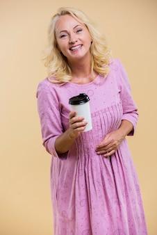 Пожилая женщина держит чашку кофе