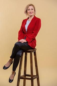 椅子でポーズ美しい年配の女性