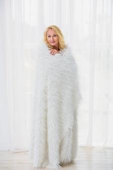 ふわふわの毛布で自分を覆う年配の女性
