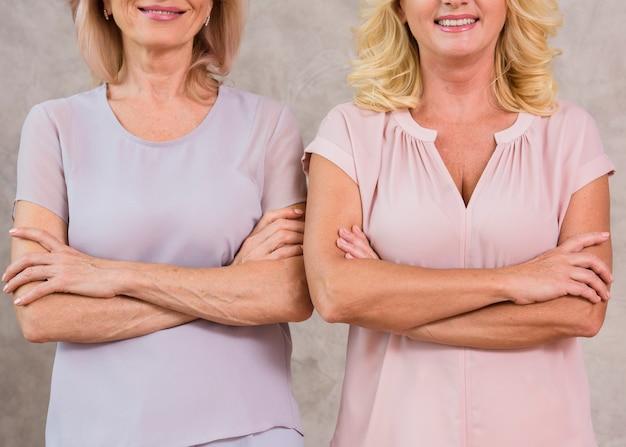 腕を組んで立っている年配の女性