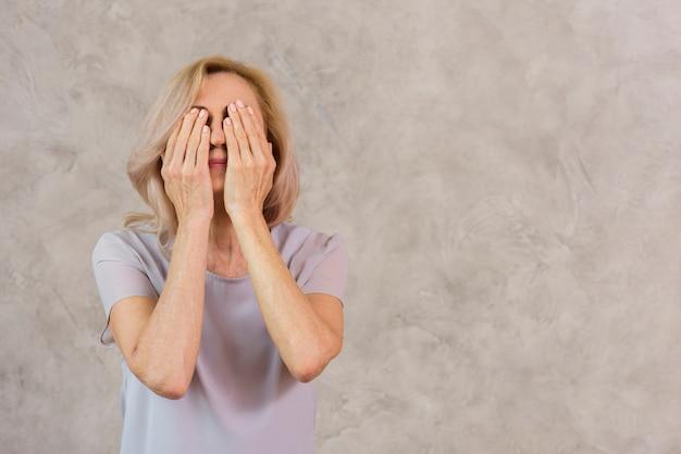 コピースペースで彼女の顔を覆っている老婦人