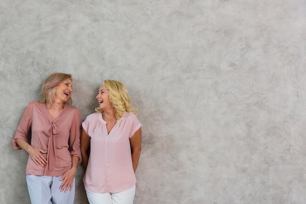 Зрелые лучшие друзья смеялись вместе с копией пространства