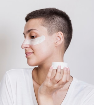 女性の顔にスキンケアクリームを適用します。