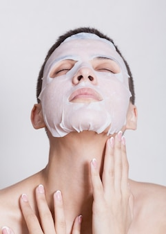 美しい女性のフェイスマスクを保湿