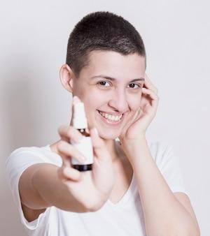 手にスキンプロダクトとカメラ目線の女性