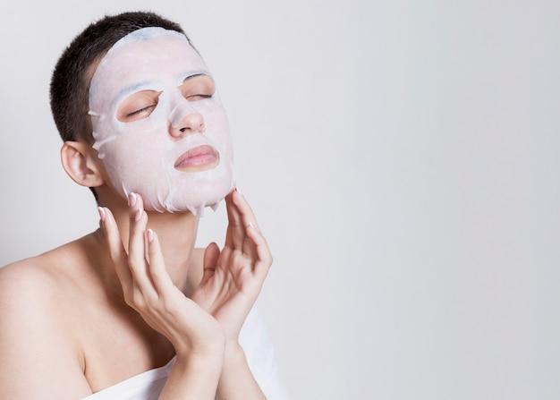 コピースペースの若い女性の保湿マスク