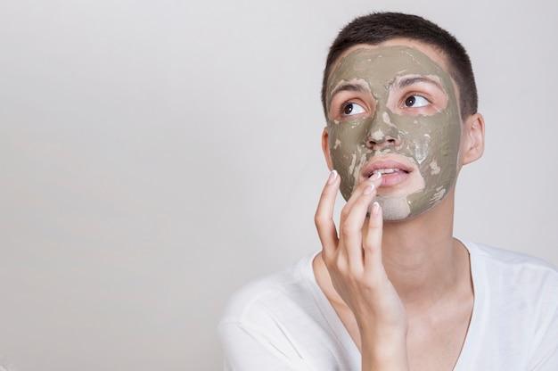 見上げる顔のマスクを持つ女性