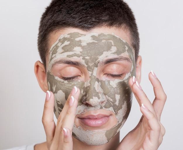 笑顔のフェイスマスクを持つ女性