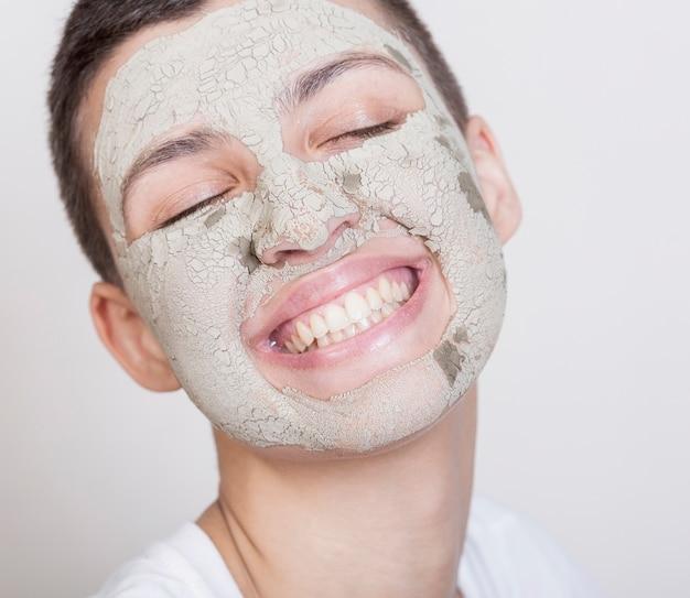 顔のマスクを持つスマイリー女性