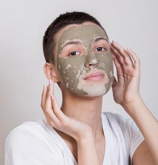 カメラを見て顔のマスクを持つ女性
