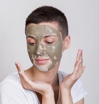 下へ見ている顔のマスクを持つ女性