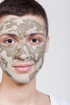 カメラのクローズアップを見て顔のマスクを持つ女性
