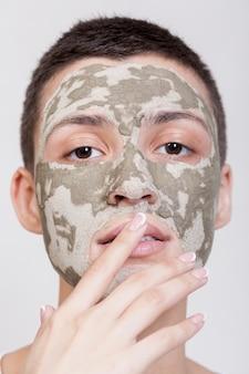 カメラのクローズアップを見て顔のマスクを持つフロントビュー女性